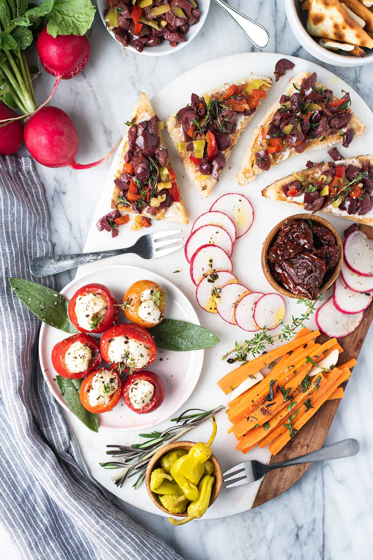party platter on white marble with olive tapenade, veggies, stuffed peppers