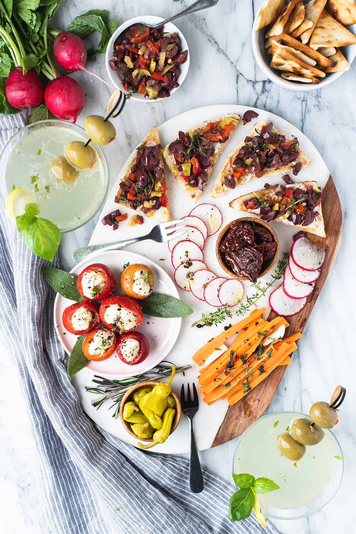charcuterie board on marble with olive tapenade, veggies, and two martinis