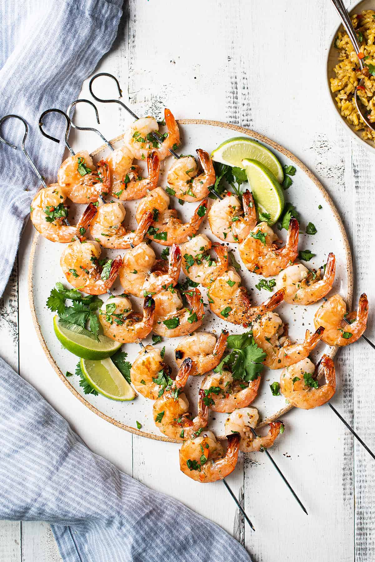 shrimp skewers on white plate with lime wedges