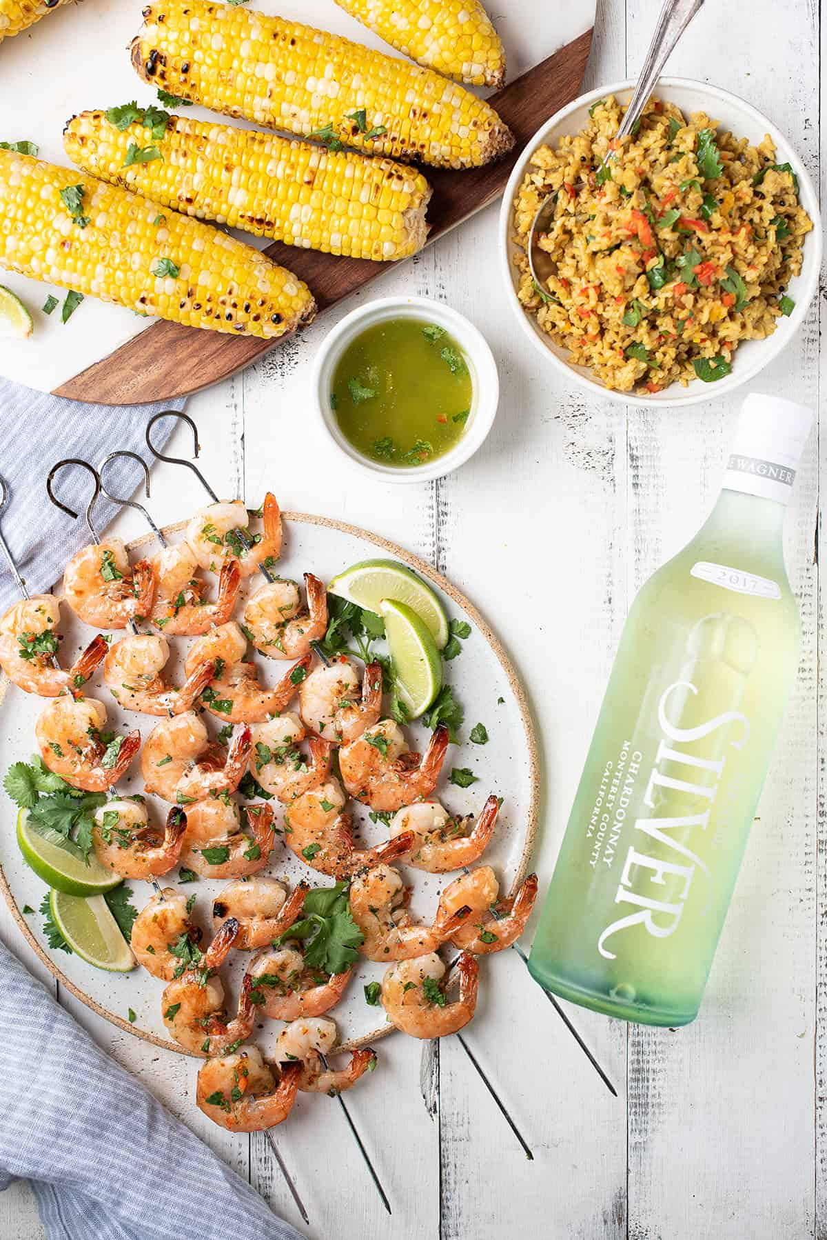 shrimp skewers on white plate with bottle of white wine, grilled corn, and rice