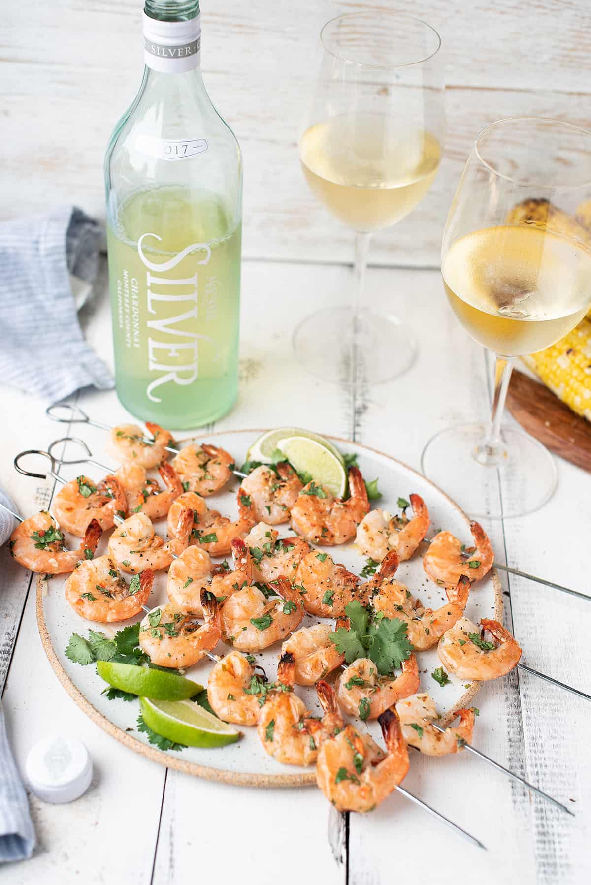 shrimp skewers on white plate with glasses & bottle of white wine