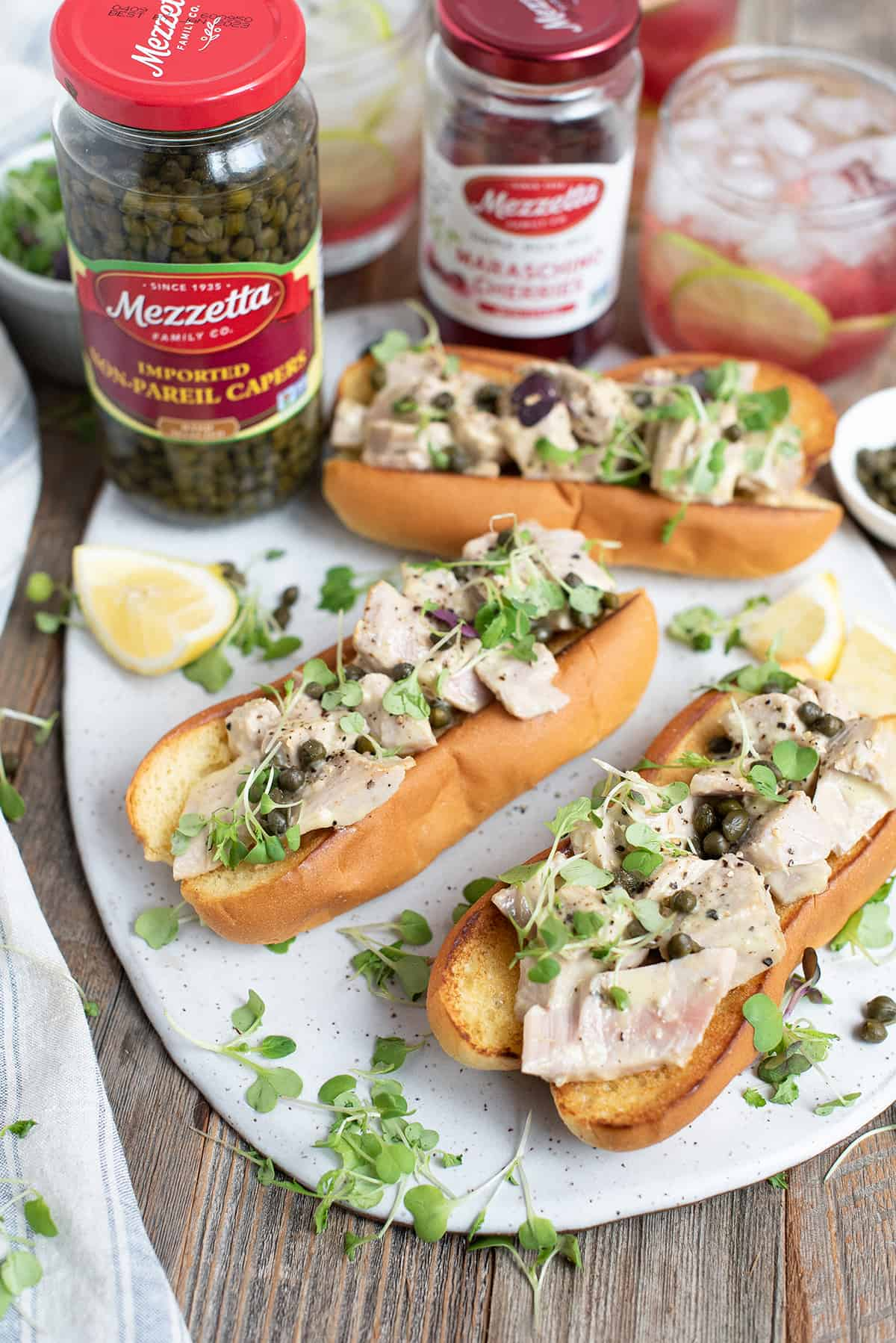 tuna sandwiches in hot dog buns on white platter with capers