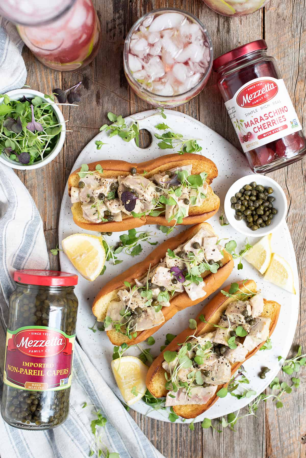 tuna sandwiches on hot dog buns on white platter with lemon slices & capers