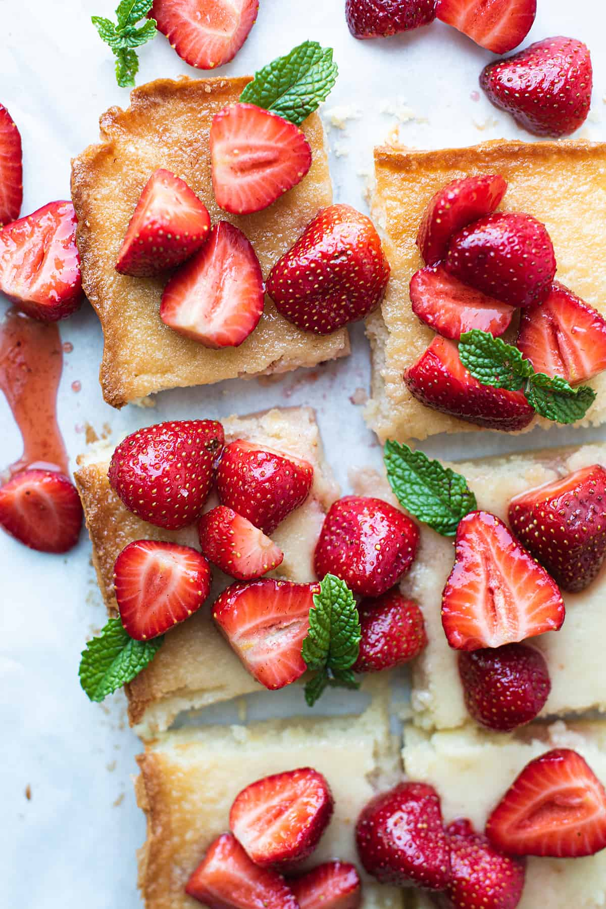close up of strawberry butter bars on white paper with mint