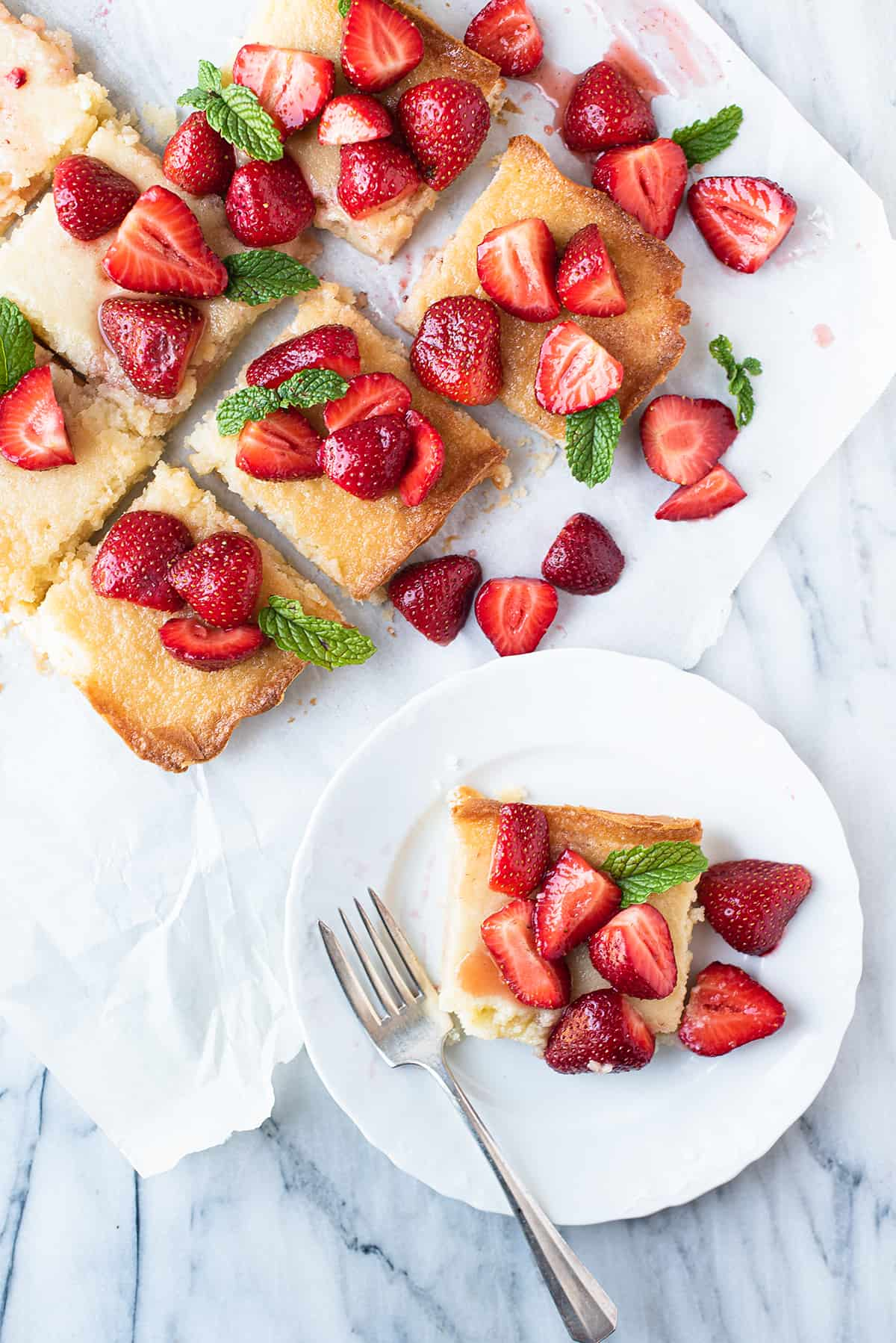 butter bars cut into squares + one on white plate, topped with sliced strawberries and mint.