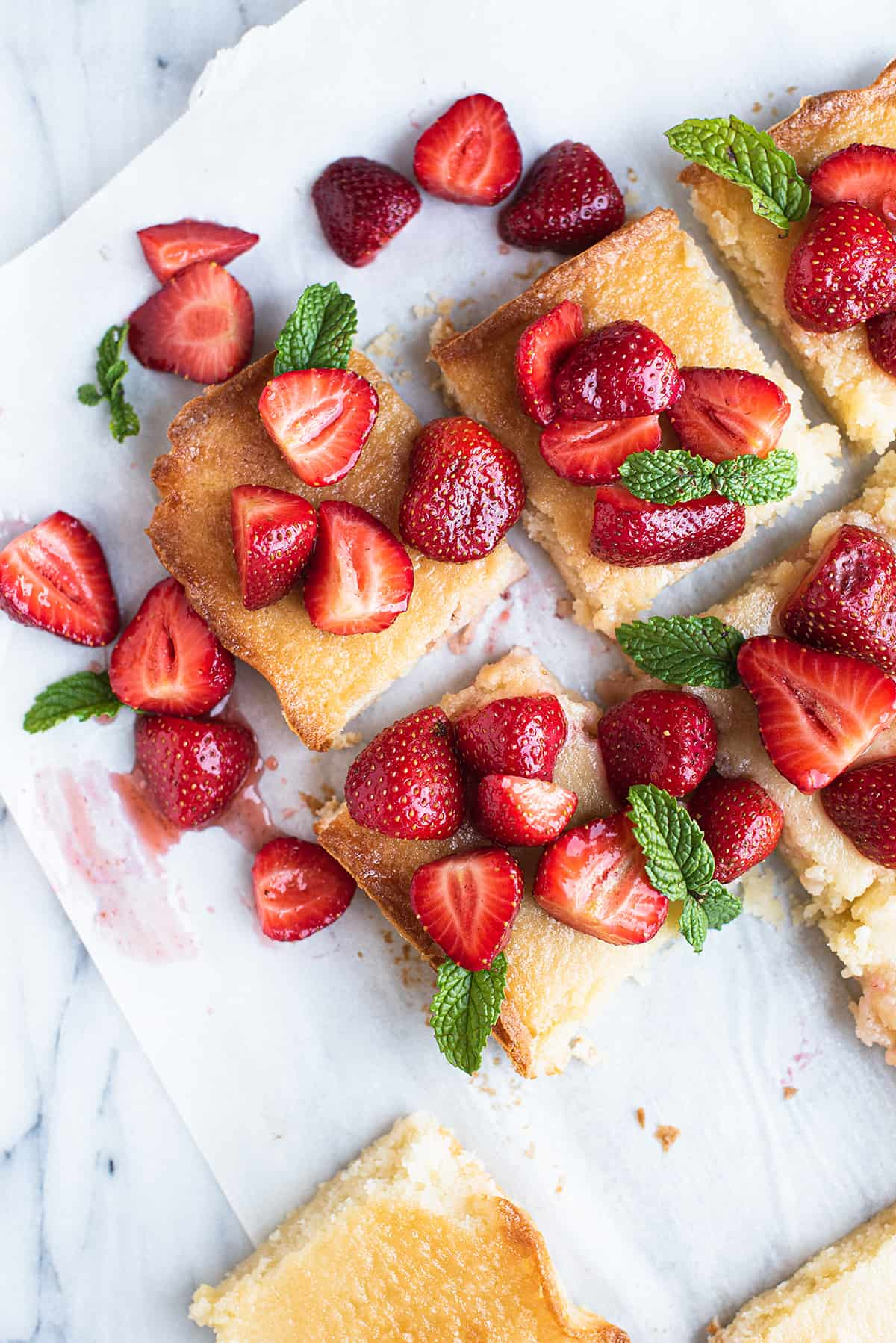 butter bars with sliced strawberries on top, on white paper with mint