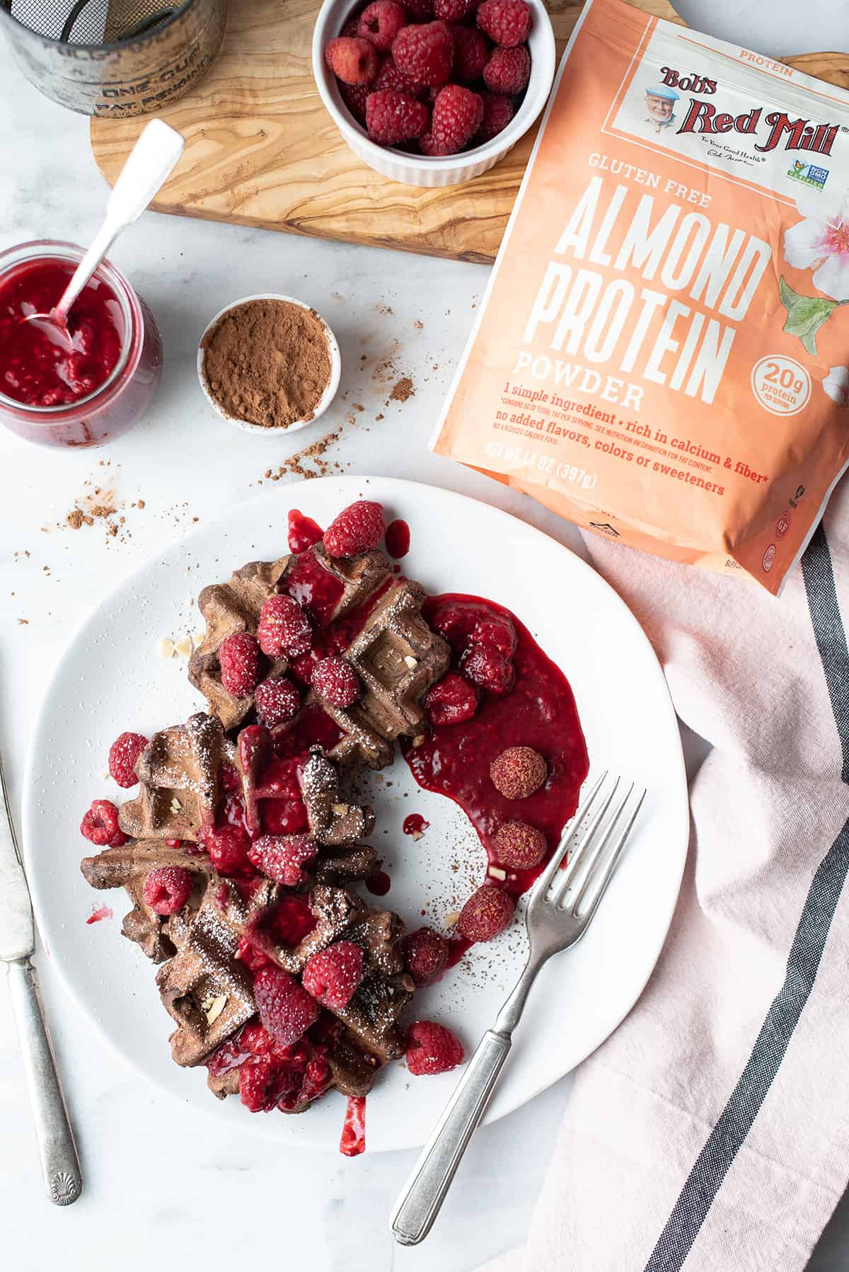 gluten-free chocolate waffles on plate, drizzled with raspberry sauce