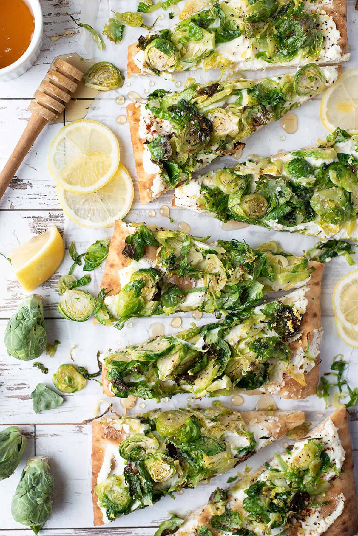 lemony brussels sprouts flatbread, sliced with honey dripping