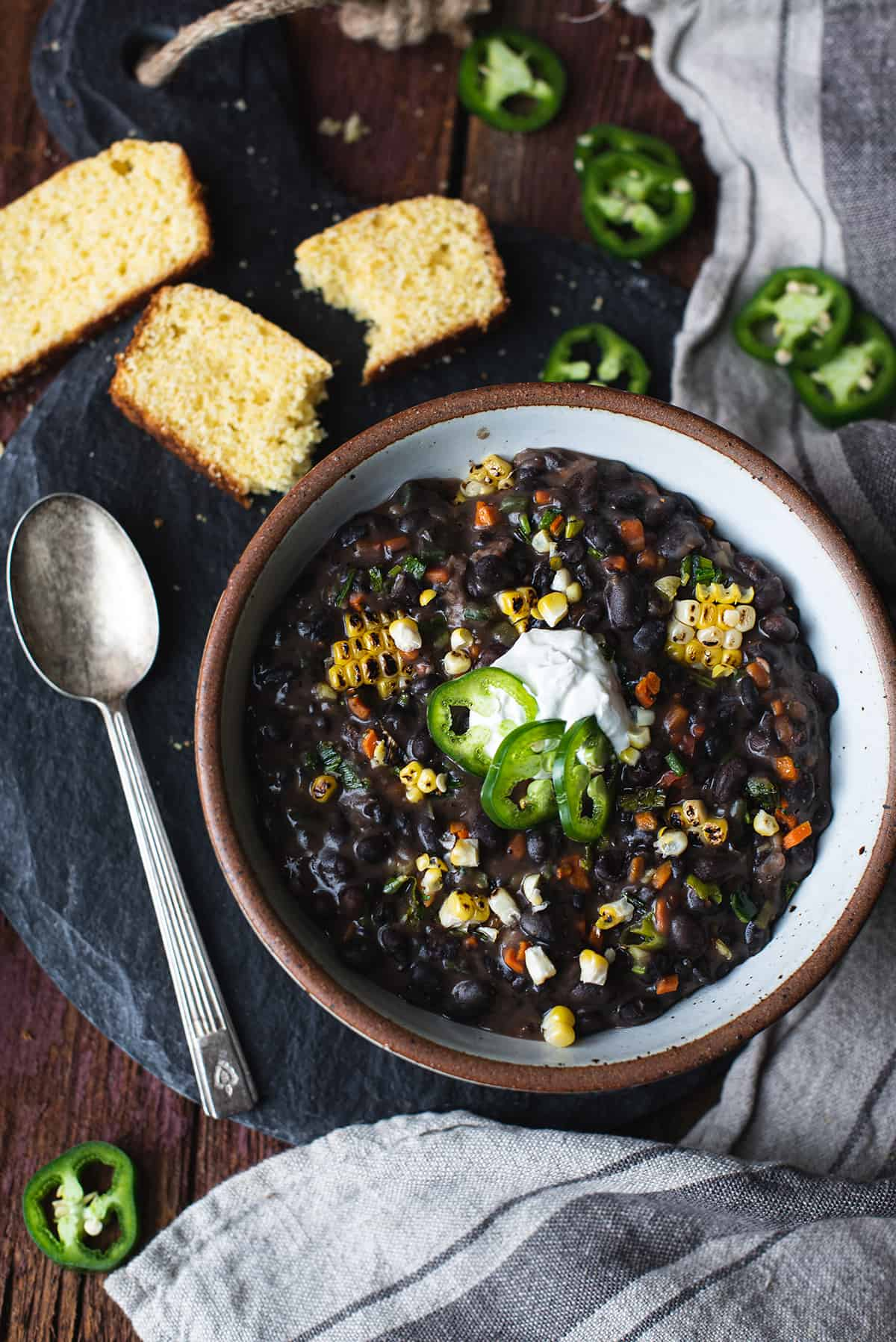 bowl of fire roasted black bean soup topped with jalapeños and cornbread