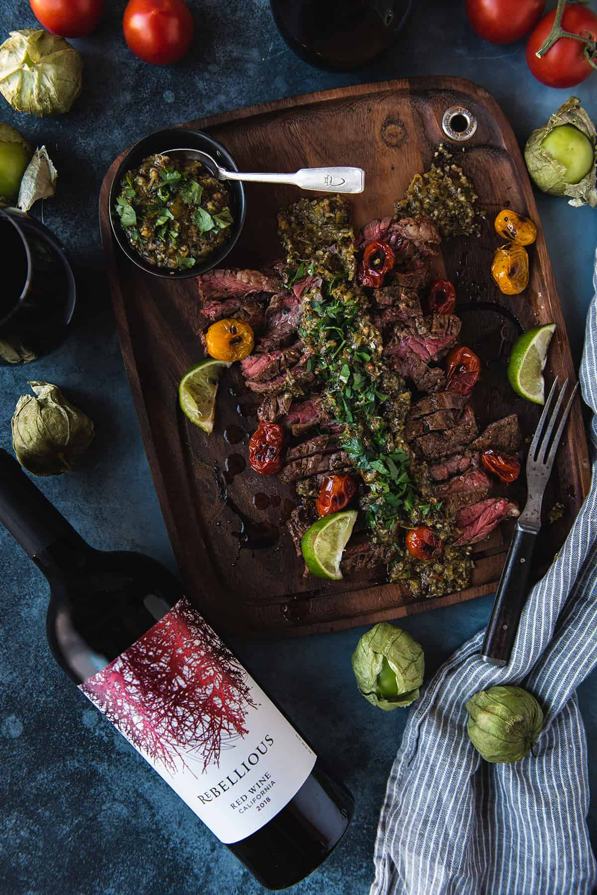 skirt steak on wood platter, chimichurri on top with rebellious wine