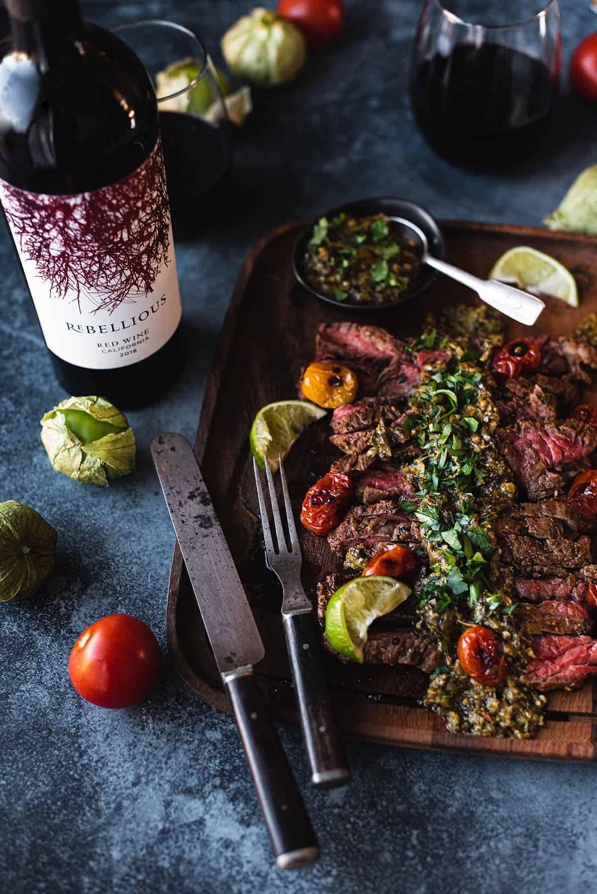skirt steak on wood platter with fork & knife + chimichurri on top