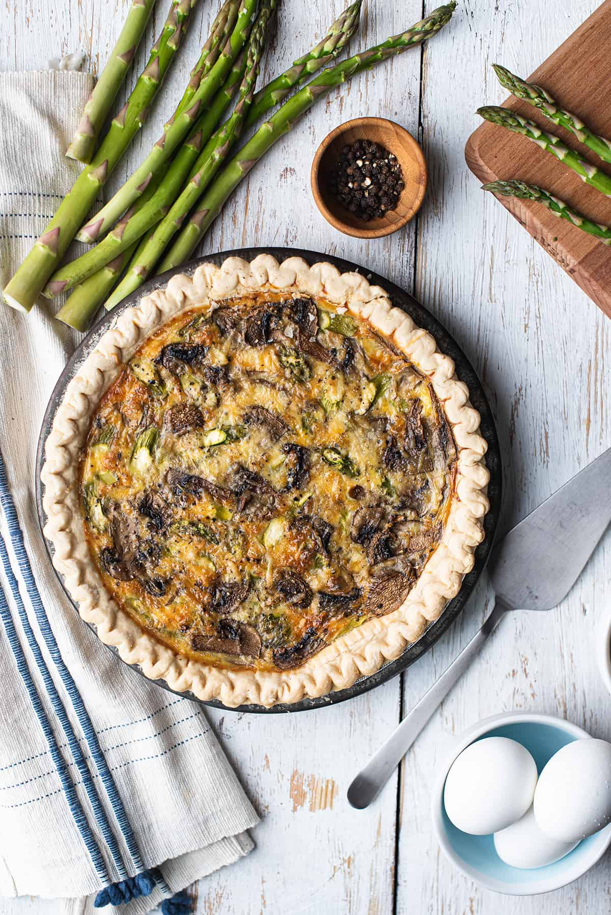 finished asparagus & mushroom quiche in pan on white board