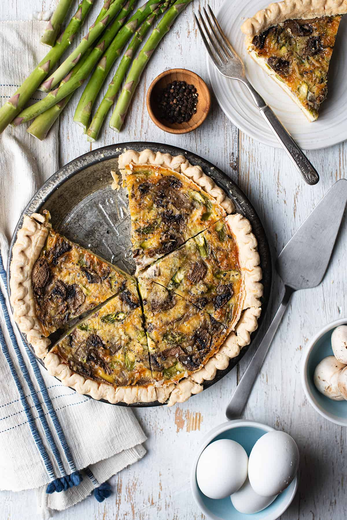asparagus & mushroom quiche sliced in pan on white wood
