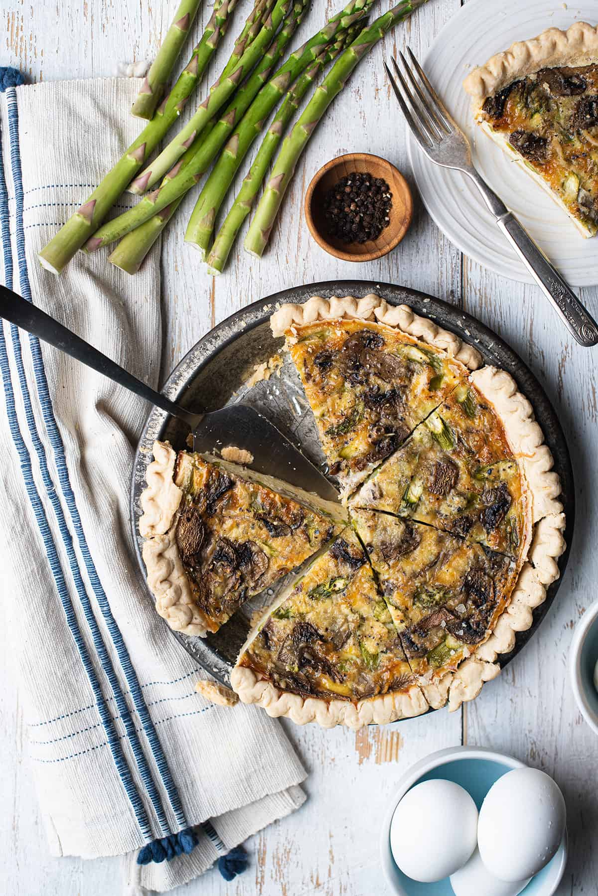 asparagus mushroom quiche sliced in pan with pie server on white wood