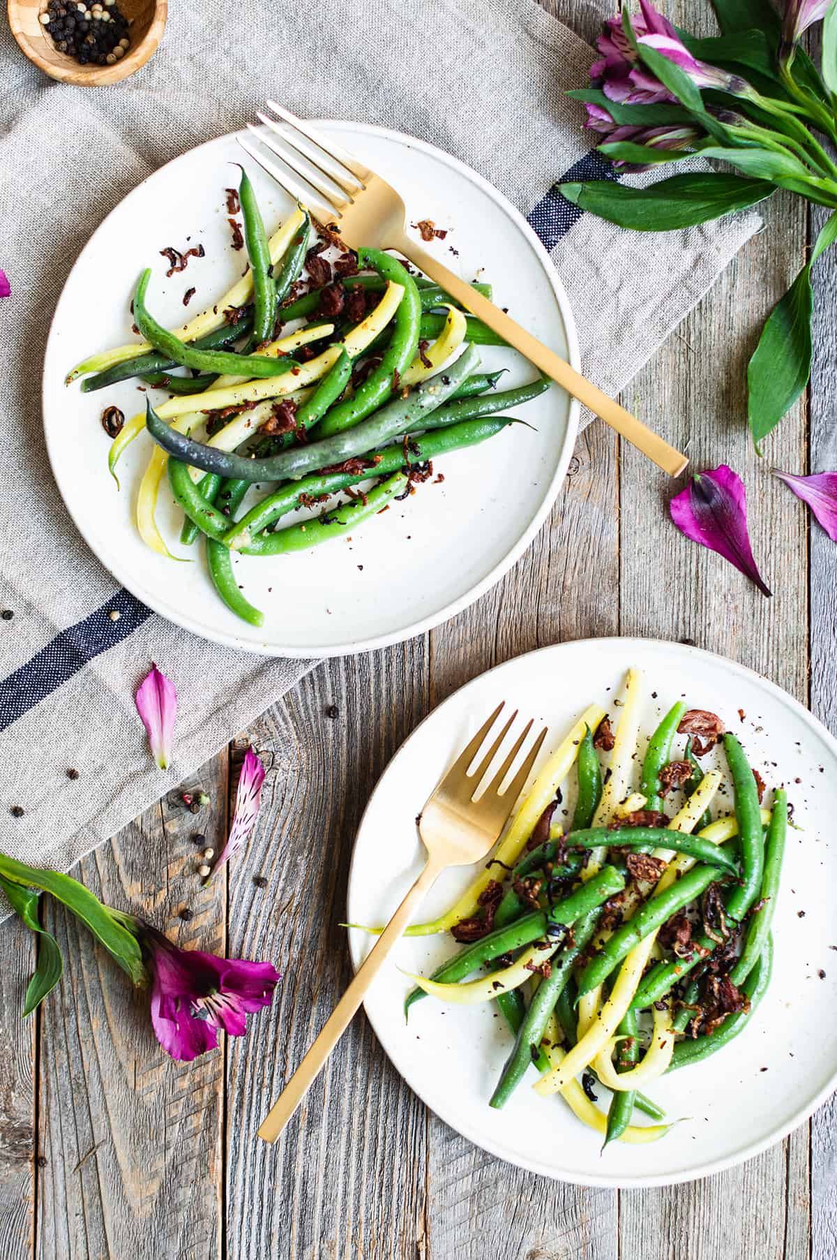 string beans on white plates with gold forks and purple flowers