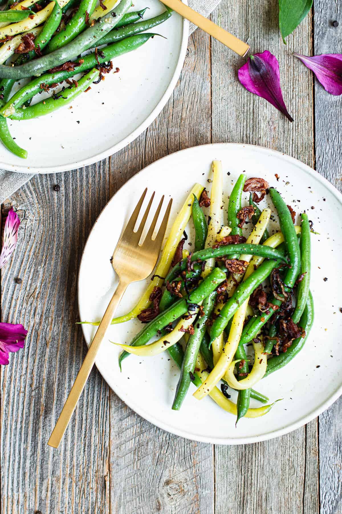 green and yellowstring beans on white plate with gold fork