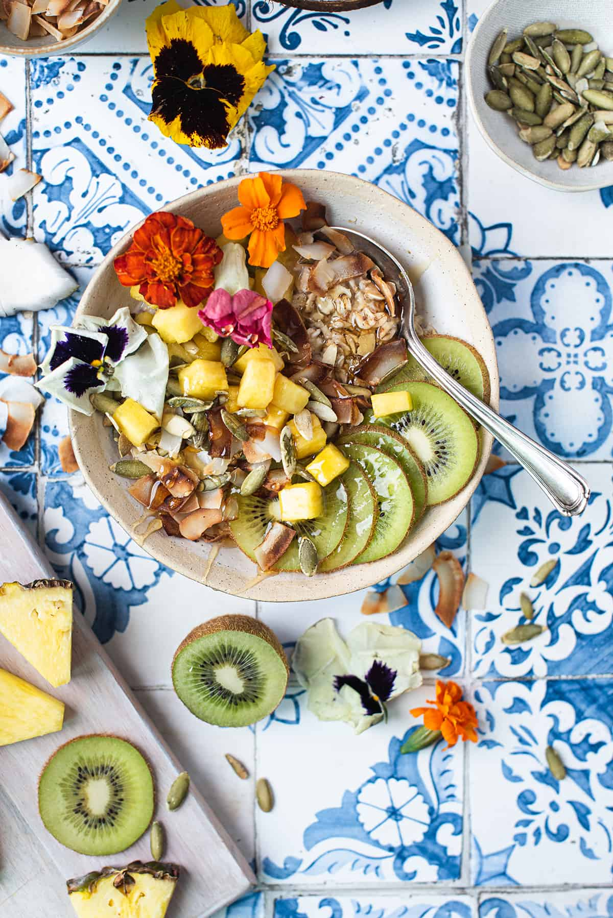 breakfast bowl topped with pineapple, kiwi, pepitas & coconut on blue pattern tile