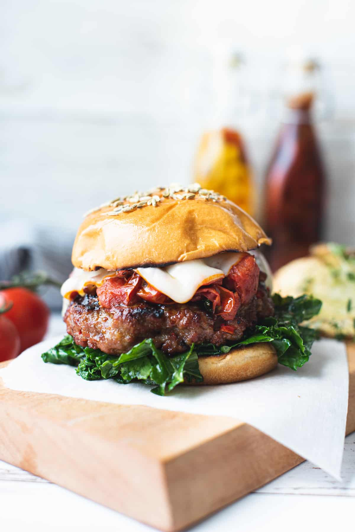 close up of sausage burger with cheese and fire roasted tomatoes on wooden platter