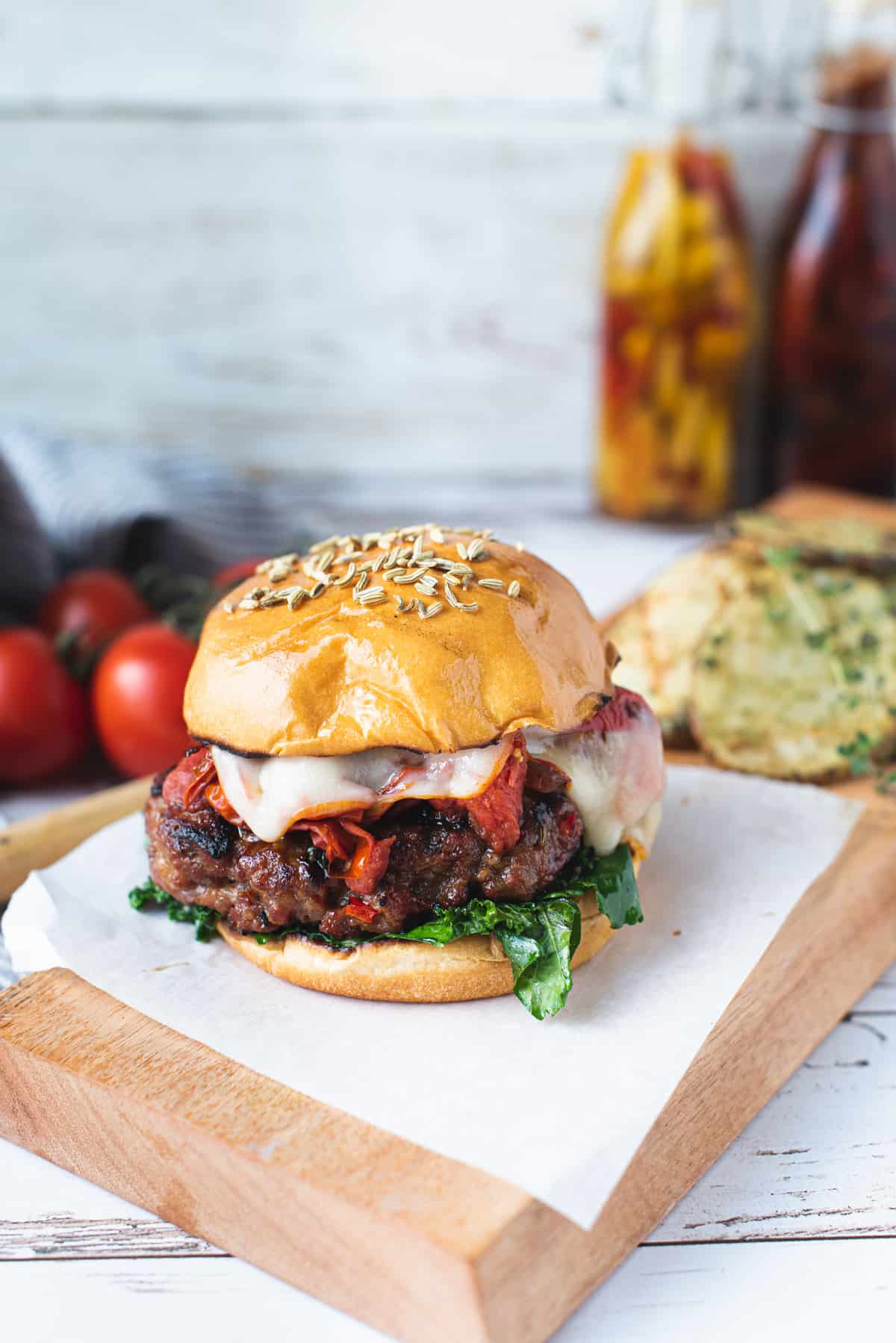 burger on a wooden platter with all the fixings