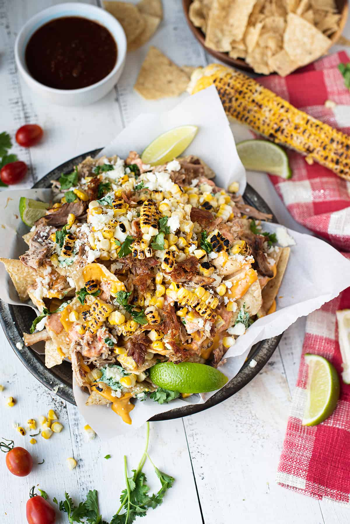 loaded nachos in pan with white paper and checkered red napkin