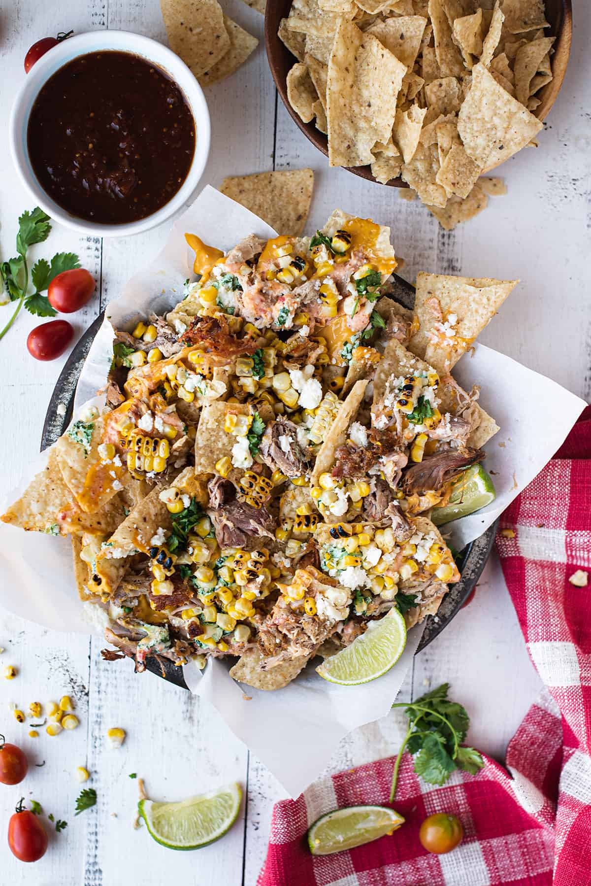 plate of loaded BBQ pork nachos on white table with red checkered napkin