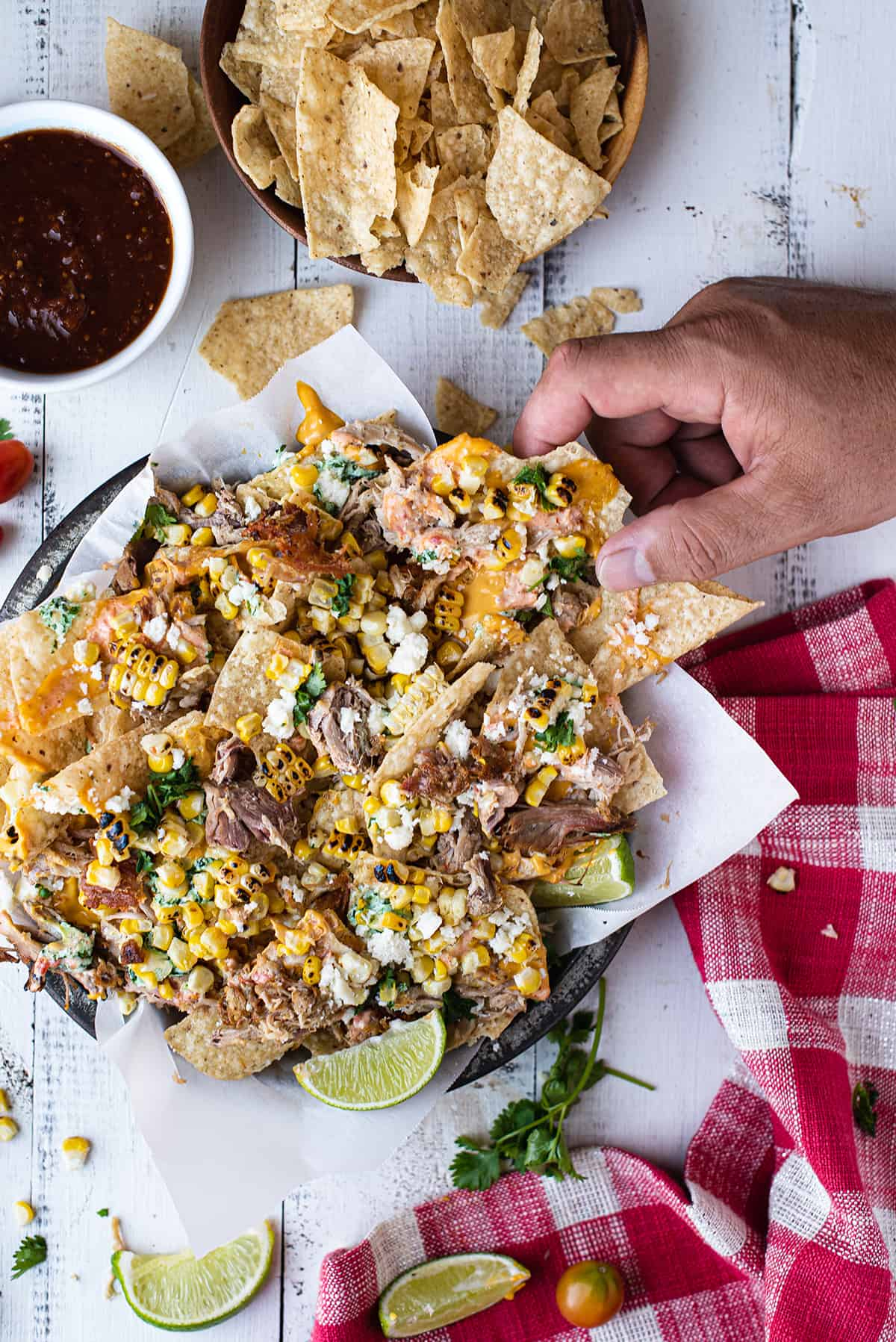 hand grabbing loaded pork nachos in pan with white paper