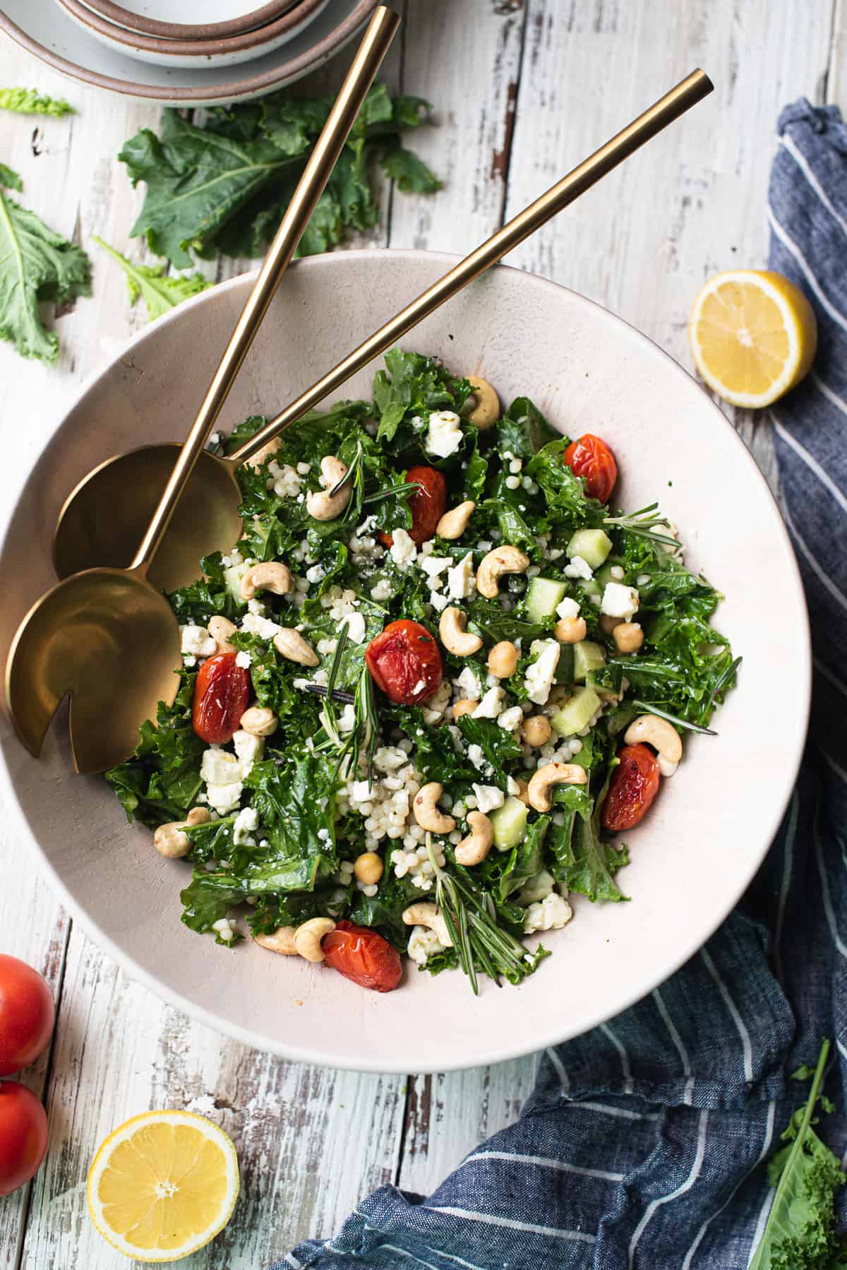 kale salad in wooden bowl with serving spoons & blue striped napkin