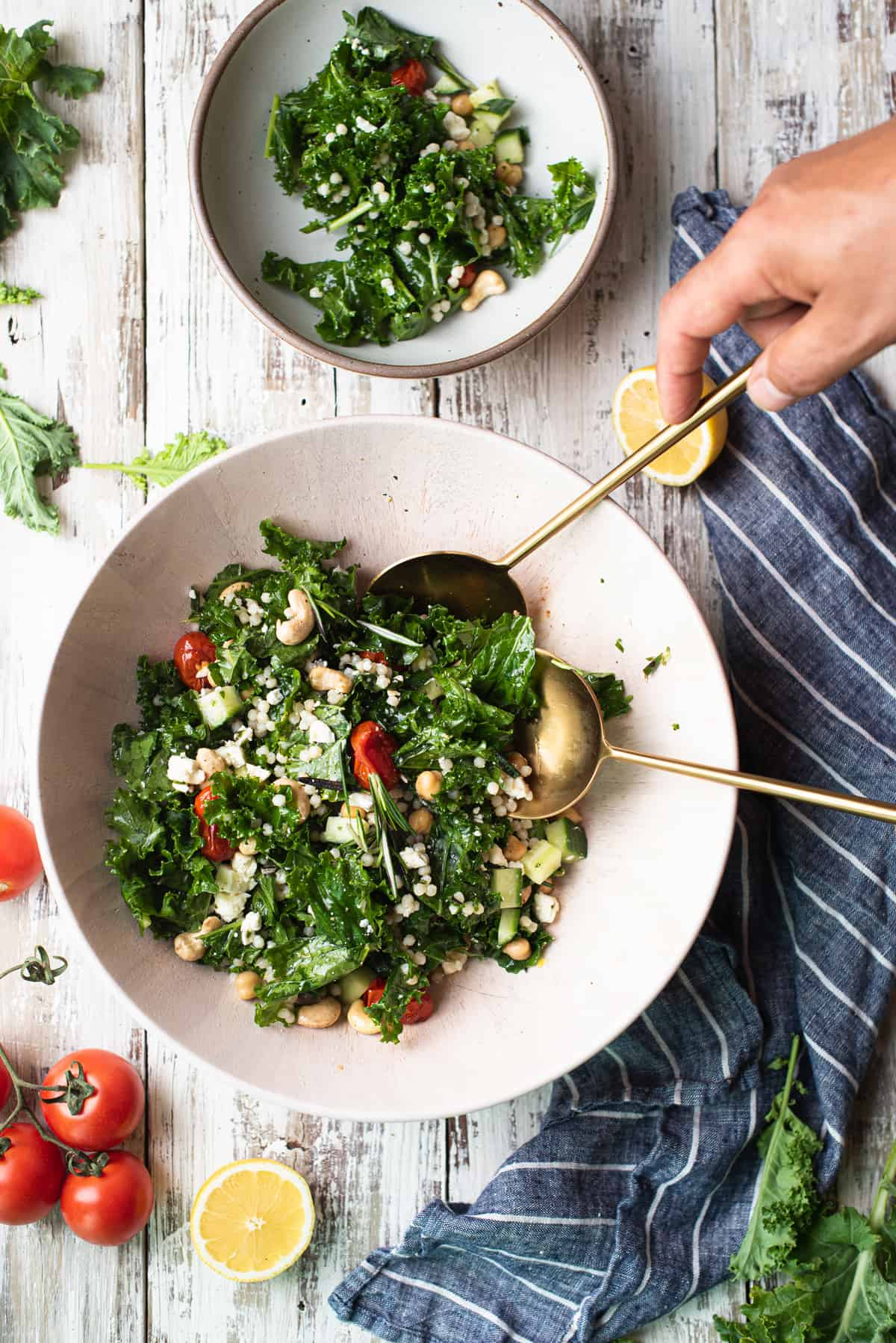 hands serving salad in wooden bowl with blue striped napkin