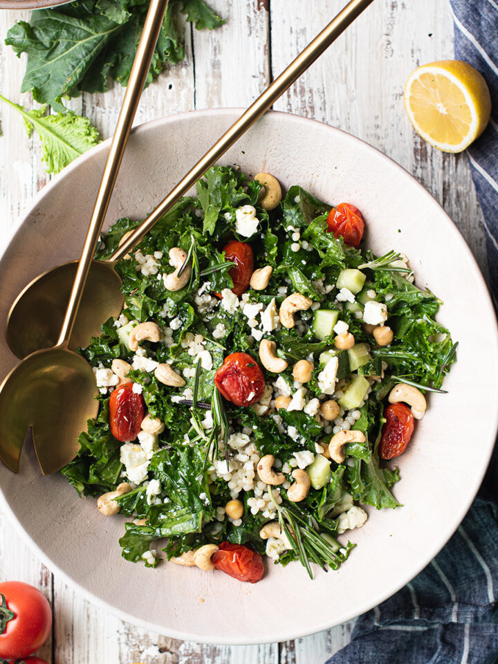 kale salad in bowl with brass serving spoons
