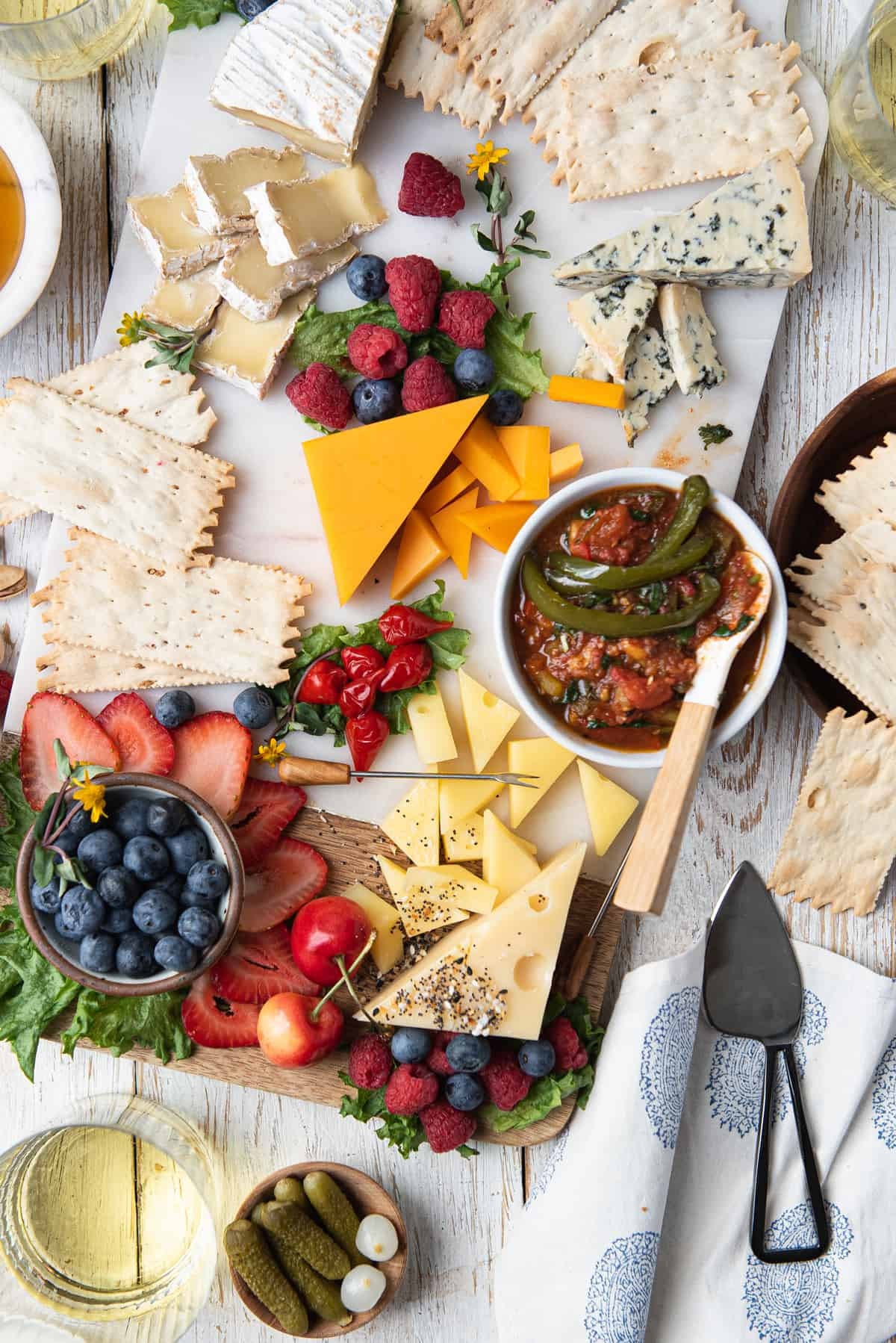 grazing board with cheese, crackers, fruit, and jalapeño jam with spoon