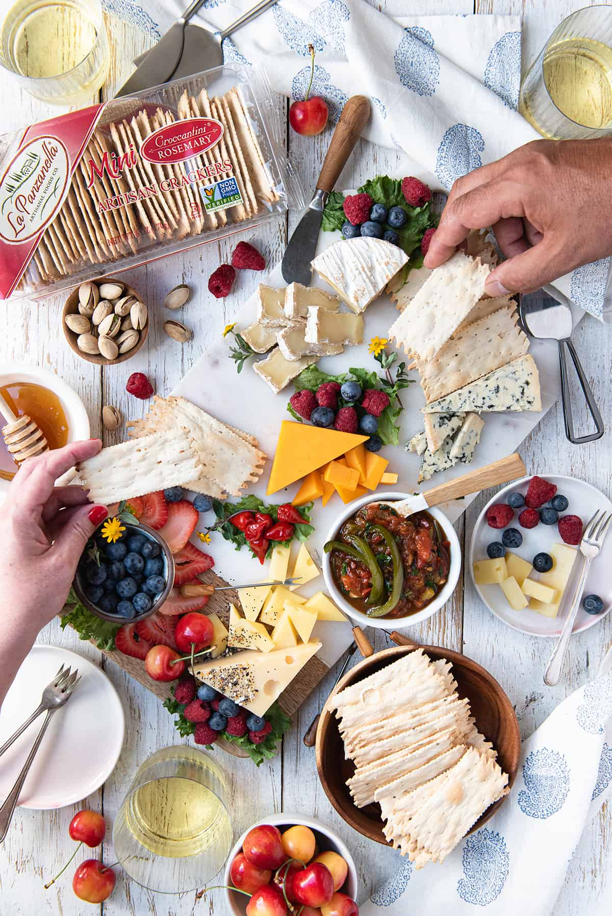 hands holding crackers on white summer grazing board with cheese, crackers, fruit