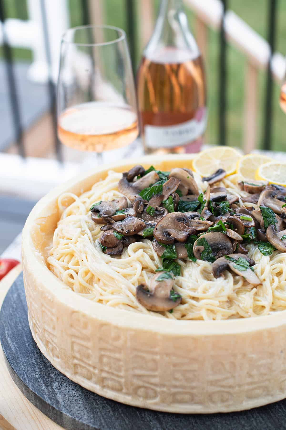 close up of pasta with mushrooms in Alfredo sauce in cheese wheel with wine in background