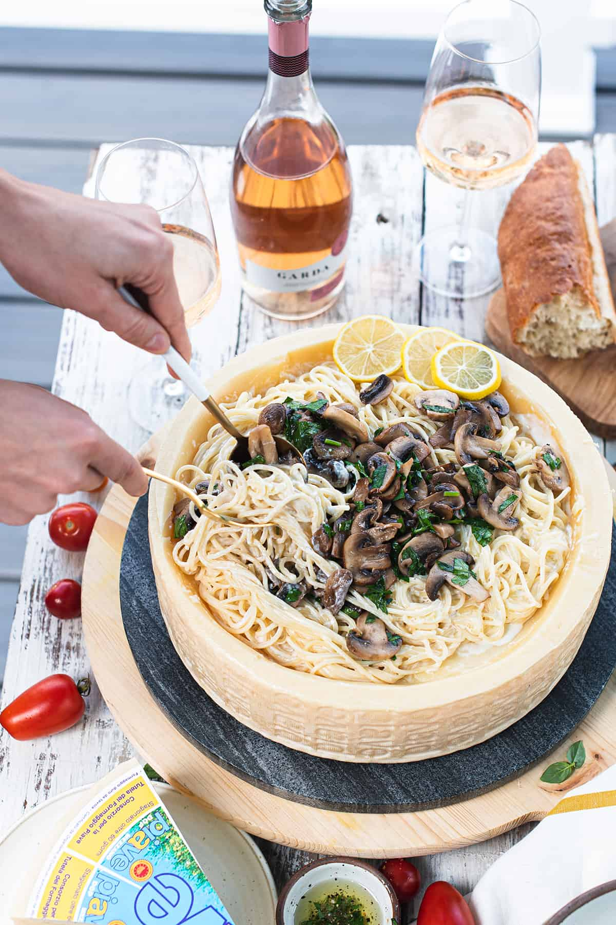 hands serving lemony Alfredo in cheese wheel on picnic table with wine