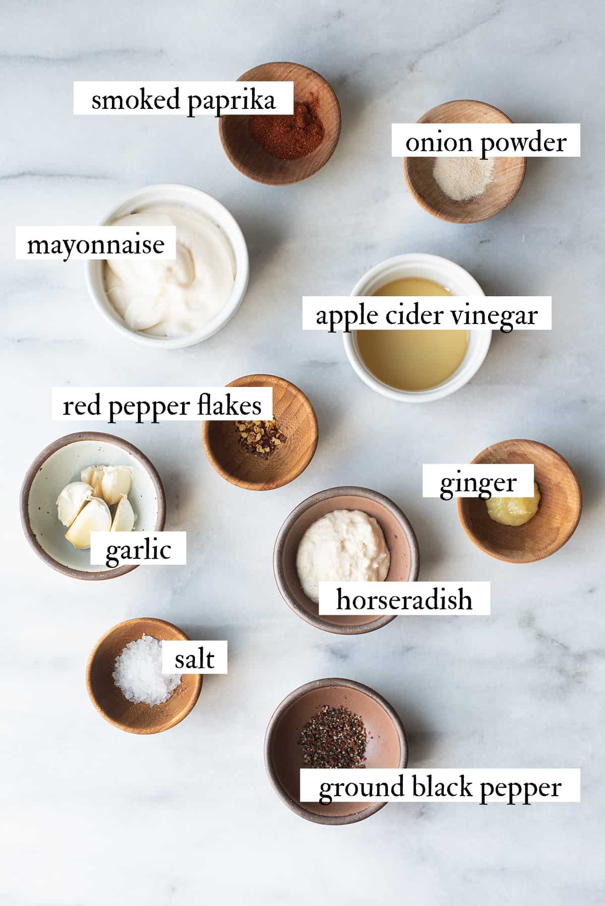 ingredients for white BBQ sauce in bowls on marble surface