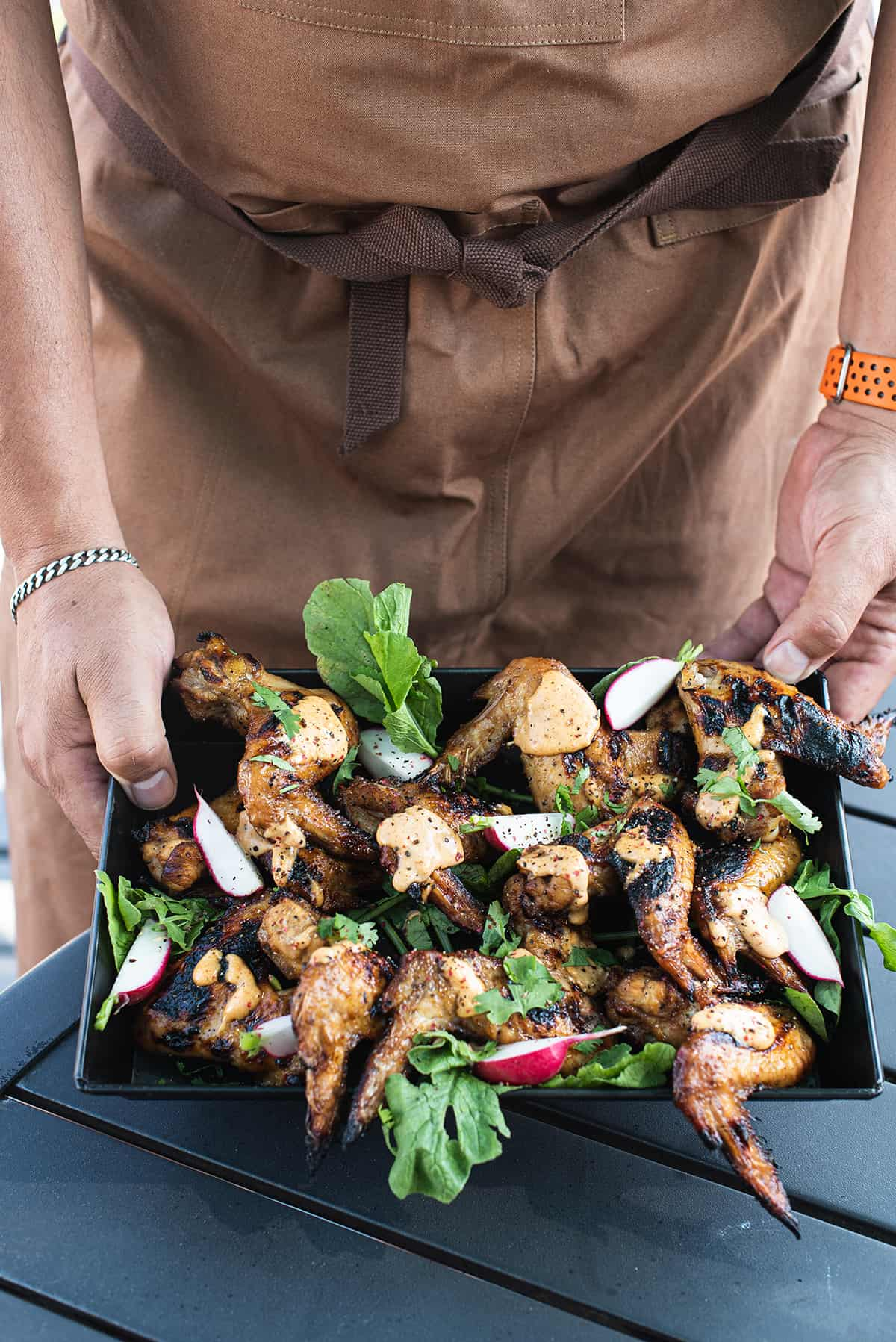 man in brown apron holding tray of chicken wings with sauce
