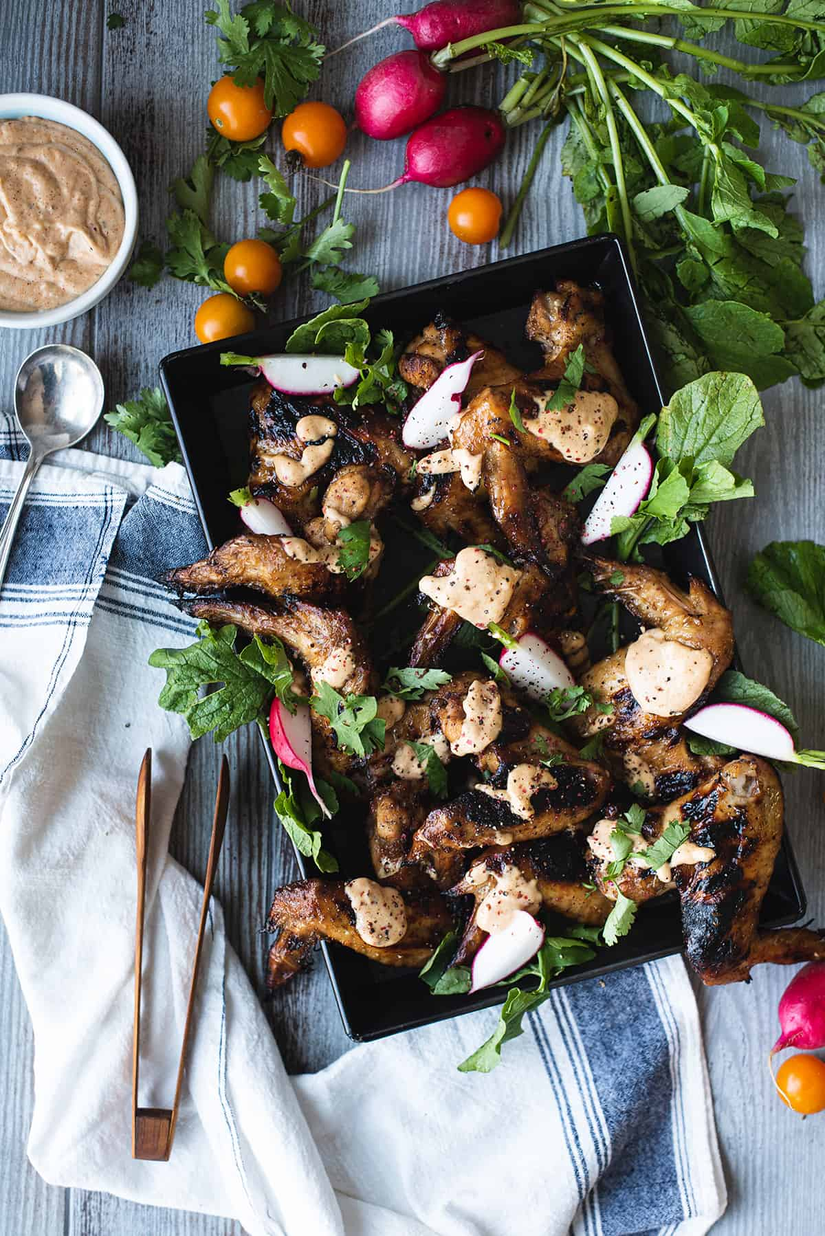 black tray of chicken wings drizzled in White BBQ Sauce with greens